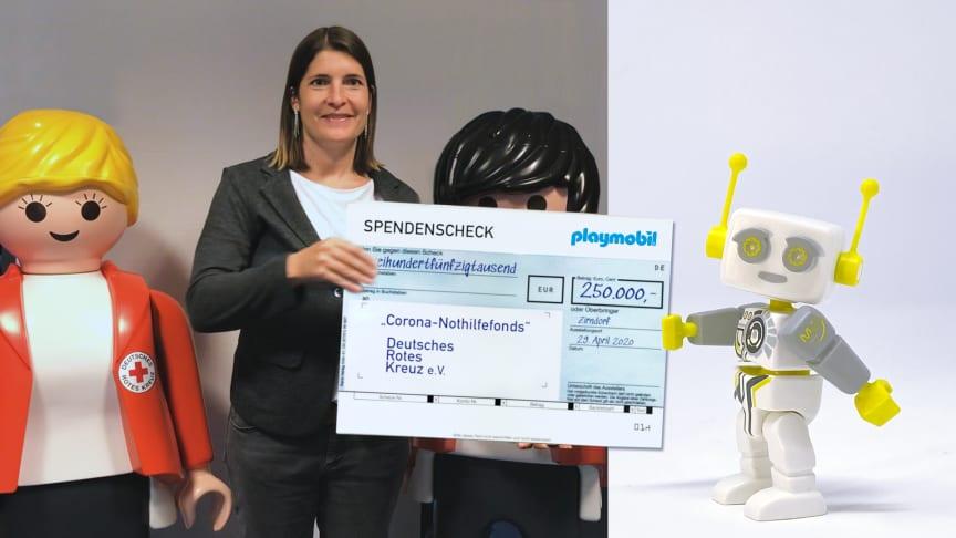 Der digitale Roboter ROBert übergibt den Scheck virtuell  an DRK-Marketingleiterin Lucy Schweingruber