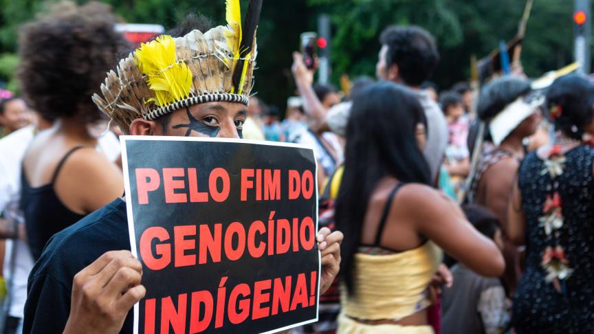 """En demonstrant holder et skilt pålydende """"for afslutningen på folkemordet imod oprindelige folk"""" til en demonstration i Sao Paulo i Brasilien - et land, hvor oprindelige folk tvangsfjernes og myrdes, så landbruget kan udvidde sin produktion"""
