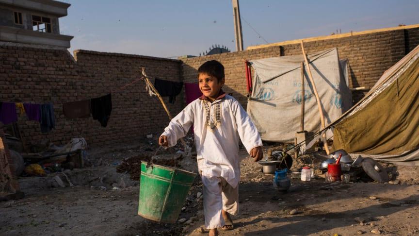 Arbaz, 6 år, bär en hink som han har fyllt med vatten, Jalalabad, östra Afghanistan.