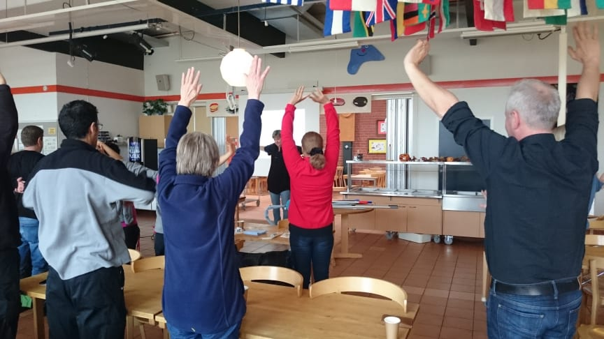 Ergonomen Sara Lindberg låter kursdeltagare göra övningar som sträcker på och mjukar upp kroppen.