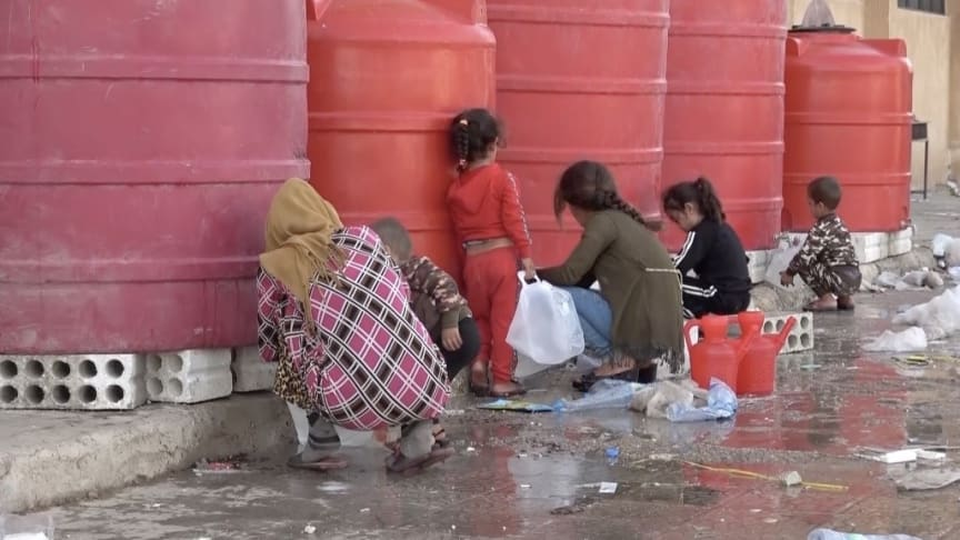A mother and children collect water in Al Hasakeh