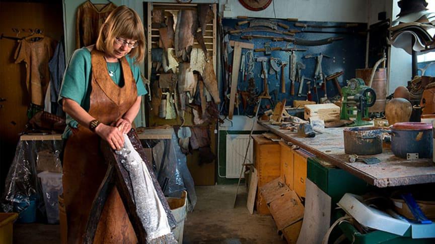 Lotta Nelson Rahme garvar ett fiskskinn i sin verkstad. Foto: Håkan Olsen. Infälld bild på Aja Pettersson.