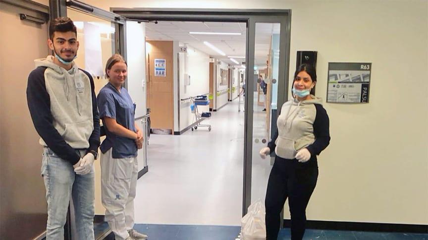Haider Beden och Sara Akbari, elever på Thoren Business School Solna, skänker matlådor till personalen på Karolinska sjukhuset i Huddinge.
