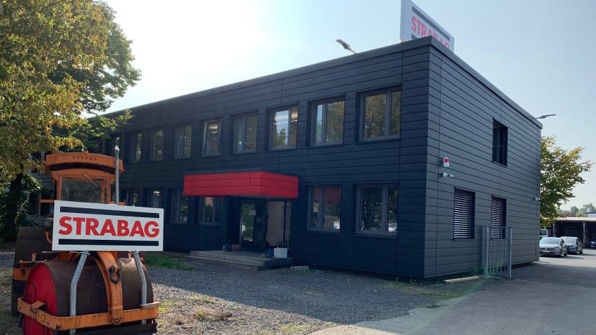 Vor dem neu gestalteten Haupteingang des Standorts Hennef weist eine historische Straßenwalze auf das Kerngeschäft der STRABAG AG hin.  Bildnachweis: STRABAG AG