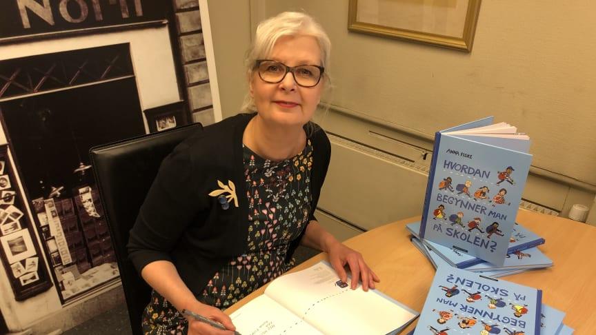 """Bildebokskaper Anna Fiske signerer en bunke av sin ferske bok """"Hvordan begynner man på skolen"""". Foto: Tanja Hoel"""