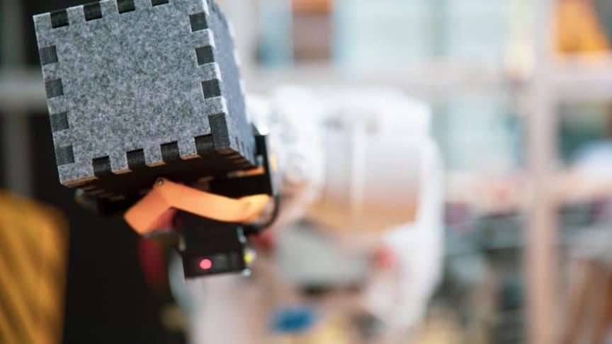 Kiertotehtaan raaka-aineina käytettäviä hylättyjä tavaroita tai roskia kuvaavat tehtaan varastossa olevat kuutiot, joita teollisuusrobotti tuo tehtaan osastoille käsiteltäväksi.