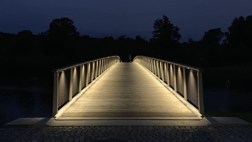 Finalist 5. Folke Bernadottes bro - Årets Stockholmsbyggnad 2020. Fox Belysning levererade 100 st små LED-puckar som är integrerade i en metallprofil under överliggaren i trä.