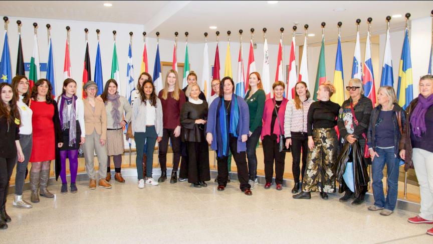 Syntolkning: Feminister från olika EU-länder samlade i Bryssel, medlemsstaternas flaggor i bakgrunden.