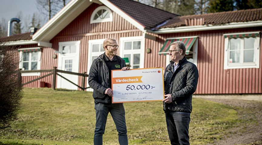 Joakim Kristoffersson, Lundsbergs Golfklubbs ordförande, tar emot check från Berry Andersson, kontorschef på bankens kontor i Storfors och Nora.