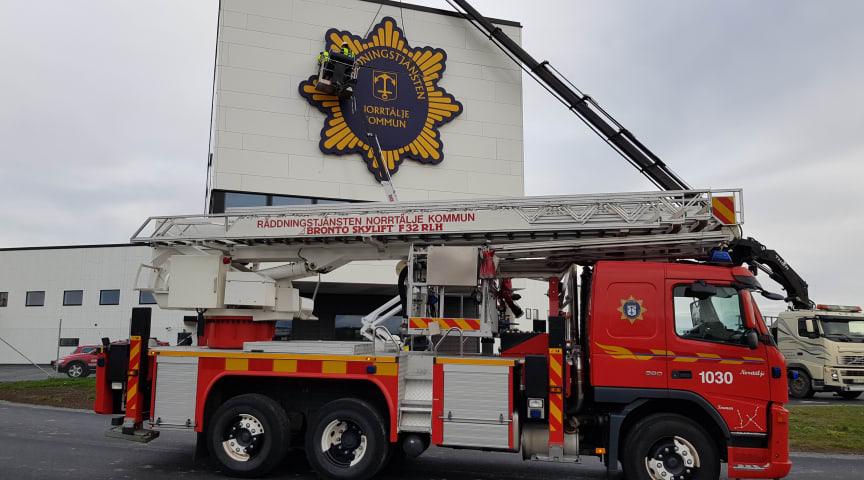 Montering av räddningstjänstens skylt på nya brandstationen.