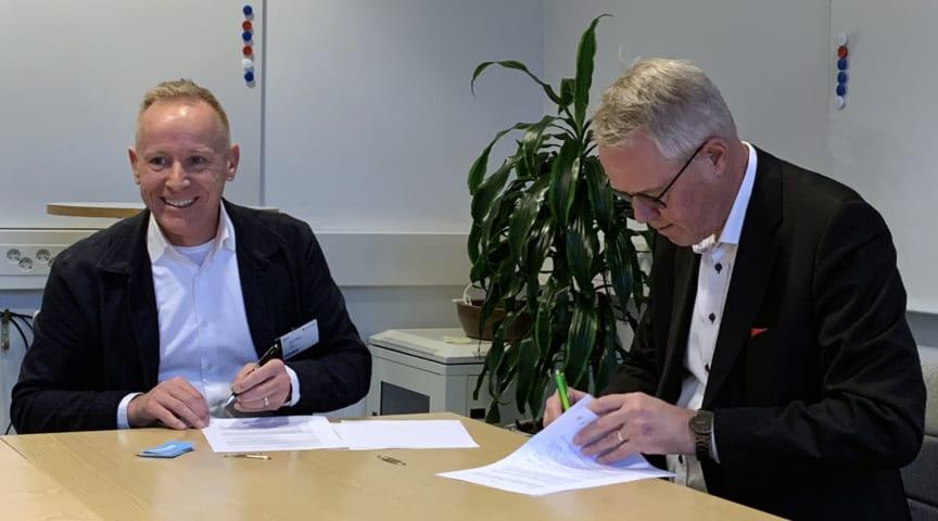 Niclas Sahlgren och Roger Sundemo skriver på avtalet