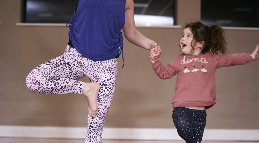 A young girl practices yoga with her mother