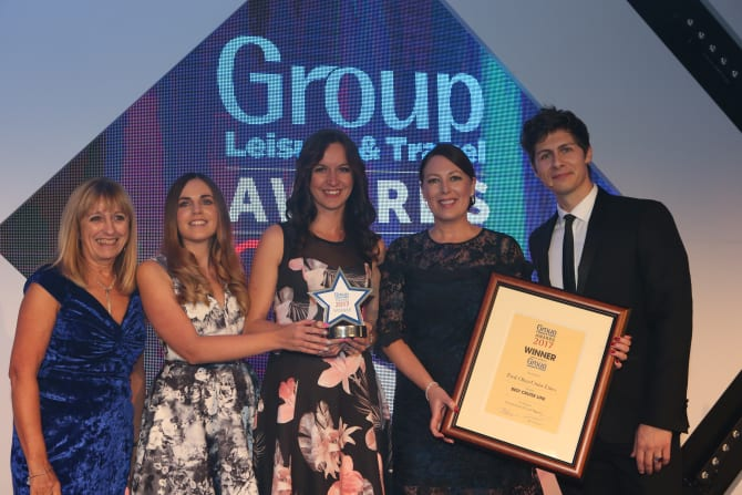 (L-R) Maureen Quinn of 'Just for Groups!' presents Sophie Thomas, Sales Executive – Groups, Hayley Walker, Sales Assistant – Groups and Ellie Fulcher, Sales Manager – Groups with the trophy alongside special guest and co-host, Magician Ben Hanlin