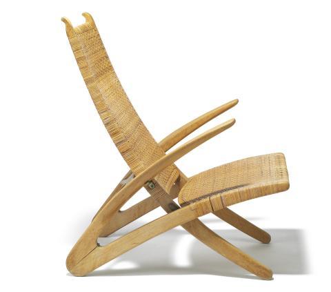 """Hans J. Wegner: """"Delfinstolen""""/""""Den lille klapstol"""". Sammenklappelig hvilestol af eg, sæde samt ryg udspændt med spanskrørsflet. Udført hos Johannes Hansen. Vurdering: 400.000-500.000 kr."""