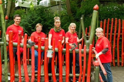 Mitarbeiter der Filiale Gera streichen das Geländer im Kindergarten neu an