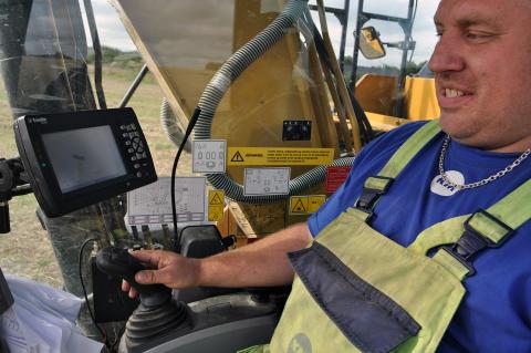Maskinfører Rasmus Søndergaard med skærmen til højre, hvor han har en 3D profil af grøften