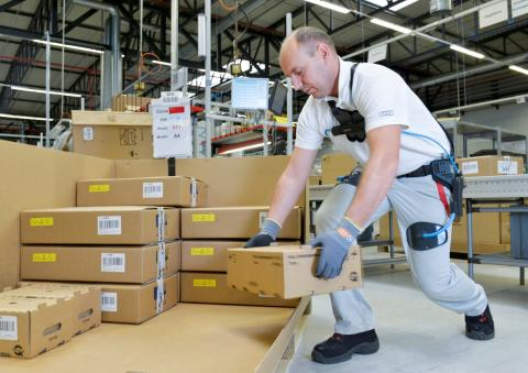 An Audi employee uses the exoskeleton when packing car components in CKD (completely knocked down) logistics at the Ingolstadt plant