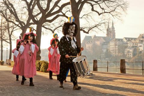 Basler Fasnacht. Tambour und Piccolospieler am Rheinufer mit dem Muenster im Hintergrund