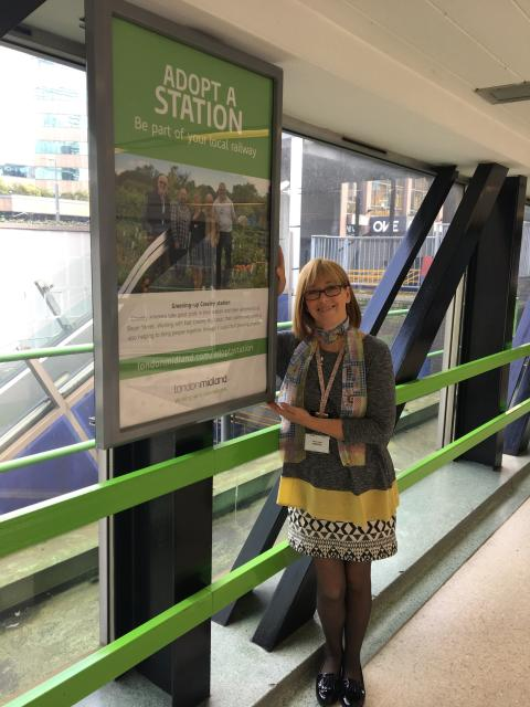 Head of community rail, Faye Lambert with newly-installed station adoption posters, at Snow Hill station.
