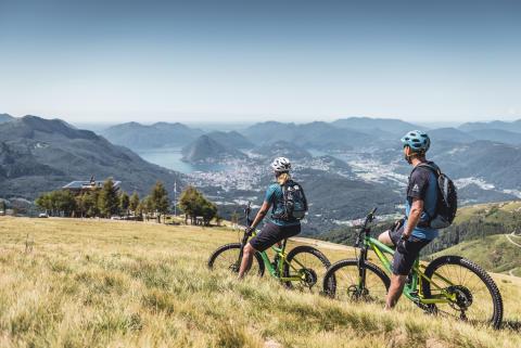 Mountainbiker geniessen das Lugano Panorama bei der Capanna Monte Bar oberhalb Capriasca