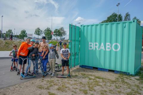 Barn och ungdomar samlade kring BRABOs utlåningscontainer i Vilunda aktivitetspark