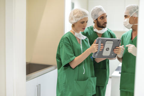 Doctors looking at a HP ElitePad 900 with a Healthcare Jacket while working HP20141219614