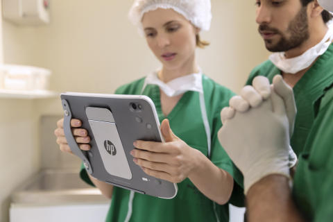 Doctors looking at a HP ElitePad 900 with a Healthcare Jacket while working. HP20141219502