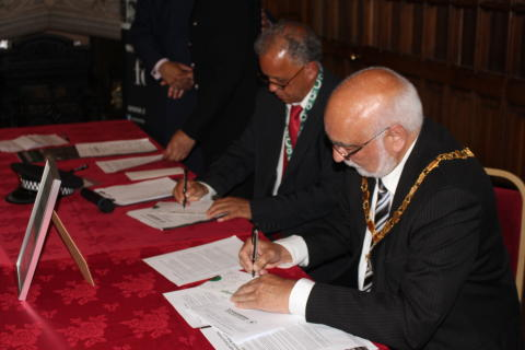 Deputy Mayor Councillor Surinder Biant and Councillor Daalat Ali sign a pledge to cohesion.