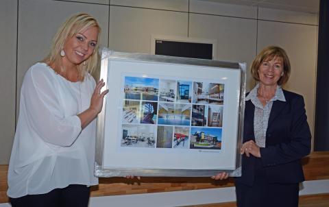 Rektor Elisabeth Palmgren mottar en bildekollasj med bilder fra skolen av Undervisningsbyggs administrerende direktør Rigmor Hansen.
