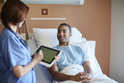 A nurse checks on a patient using a HP ElitePad with a Healthcare Jacket. HP20150513482