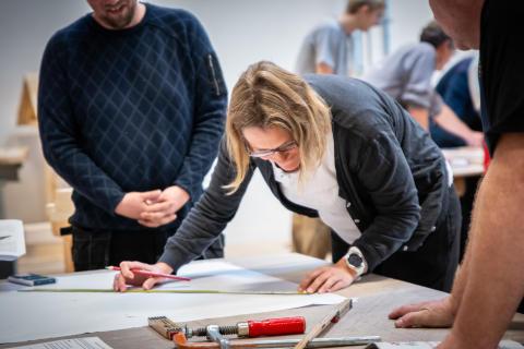 Lærer studerer arbejdstegninger på tømreruddannelsen