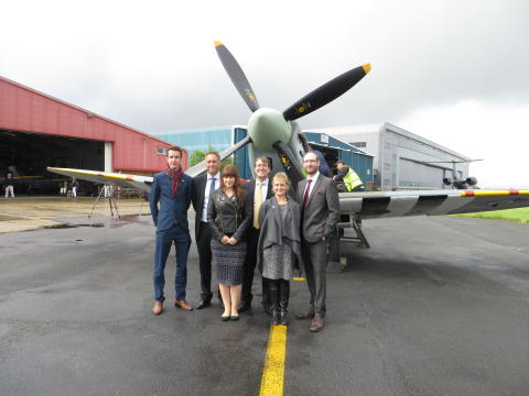The London Mint Office Team in front of a Spitfire