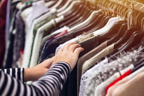 22763846-woman-browsing-through-clothing-at-second-hand-street-market