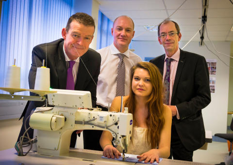 ALL sewn up: Kerry Travi showing off her sewing skills to Jim Taylor , Rochdale Borough Council's chief executive, David Moore, managing director of Headen & Quarmby and leader of the council Councillor Colin Lambert