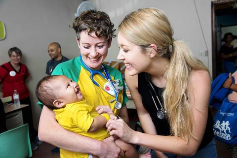 Två av Operation Smiles medicinska volontärer gullar med en av sina små patienter i Honduras.