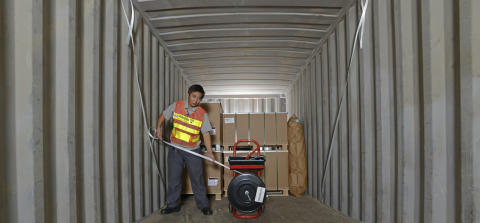 Male worker in cargo container at the port of Shanghai