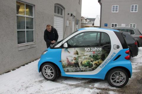 """Mit dem """"50 Jahre Jugend forscht E-Smart"""" trifft das Patenunternehmen Bayernwerk ehemalige bayerische Preisträger, hier Jürgen Geist, und lässt diese das Elektroauto signieren."""