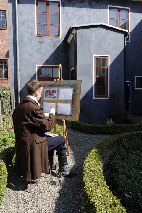 Kulturens bildpedagog målar vid staffli i Thomanderska trädgården