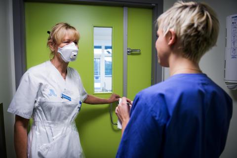 Sjuksköterskan Helene Andersson på väg in genom slussen till ett patientrum på infektionskliniken. I förgrunden undersköterskan Lisa Rosén.