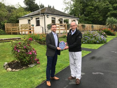VisitScotland Regional Director, Gordon Smith, presenting the Five Star plaque to Bob Hill, Sites Director at The Camping and Caravanning Club