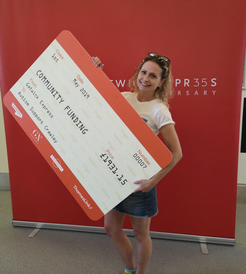 Maria Cook, Chairperson of Autism Support Crawley (left) takes delivery of a 'rail ticket cheque' from Gatwick Express