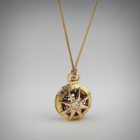 """Kim Färm (f. 1974) """"Kompass Ur"""". Kompasshänge med guldkedja. Guld, diamant."""