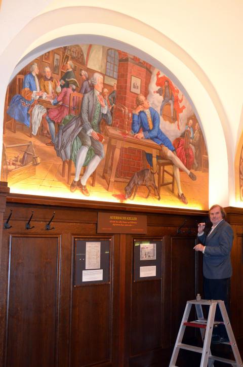 "Künstler Volker Pohlenz signiert das Wandgemälde ""Goethes Faust-Inspirationen"" in Auerbachs Keller"
