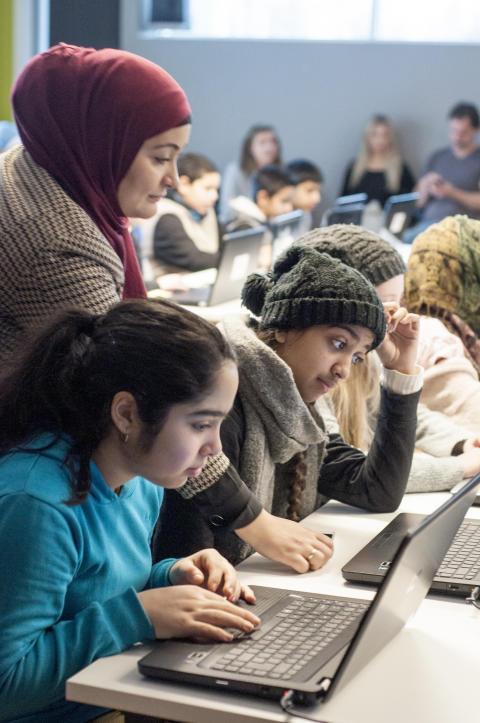 Prosjektleder i LIN, Rabia Musavi, hjelper elever med koding
