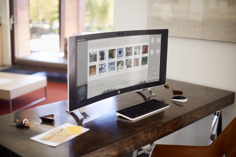 A HP ENVY Curved sitting on a desk with a music screen
