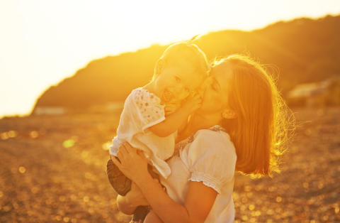 8899387-happy-family-mother-and-baby-girl-daughter-on-beach-at-sunset