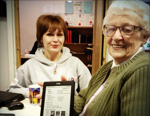 Angharad helps Marj to use her new Kindle at a Digital Friday event in Caerphilly