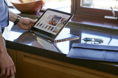 A man looking at a HP Spectre x360 Special Edition while in the kitchen next to a HP 13.3 Leather Sleeve HP20150901994