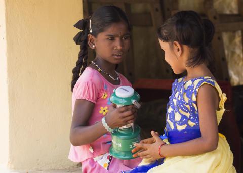 Prathibha och Swathi med familjens solcellslampa