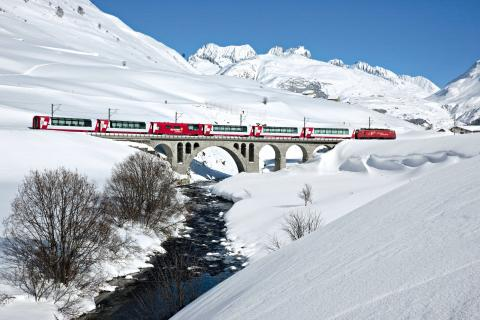Der Glacier Express überquert im zugeschneiten Urserental in der Nähe des Dorfes Hospental im Kanton Uri die Furkareuss